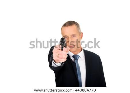 Serious mafia agent aiming by handgun - stock photo