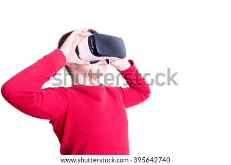 Serious male child in red long sleeve shirt holding and looking through virtual reality glasses over white background - stock photo