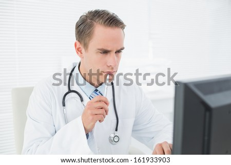 Serious male doctor looking at computer at medical office