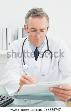 Serious male doctor writing a report at desk in medical office