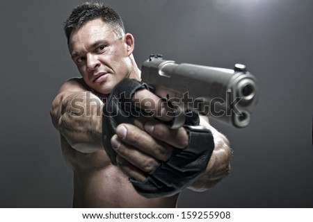 Serious Male Holding a Gun - stock photo