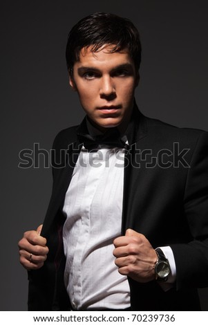 Serious male holding his jacket from a formal suite and looking at camera