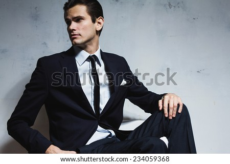Serious man in a black business suit sitting on a white chair on a white grungy background. Studio shoot
