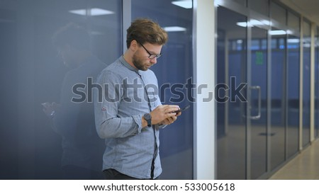 Serious man in black pants standing at the glass wall in an office building and writing business sms on mobile phone.