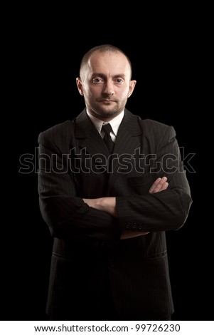 Serious man in black suite whit arms crossed