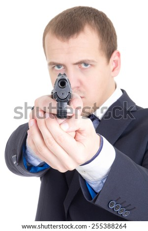 serious man in business suit aiming gun at camera isolated on white background - stock photo