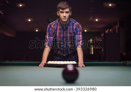 serious man in cool shirt prepares for start of game billiard balls with triangle - stock photo