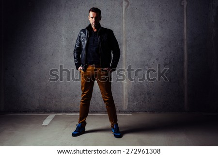 Serious man in leather jacket looking at camera, standing in empty garage against concrete wall