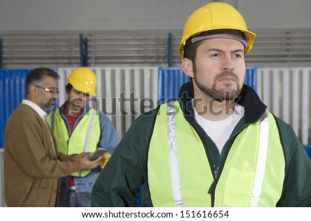 Serious man in protective wear with colleague in background at factory - stock photo