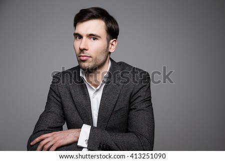 Serious man in suit on dark background
