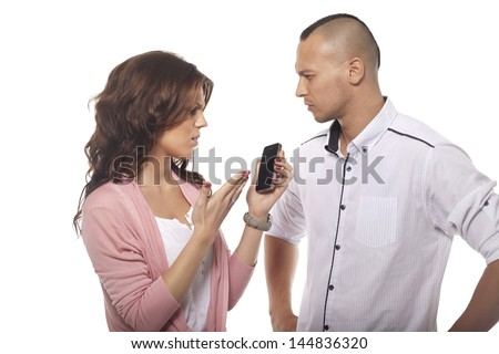 Serious Man Looking At Woman Pointing At Phone On White Background