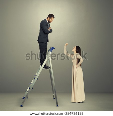 serious man looking down at emotional young woman. photo in grey room - stock photo