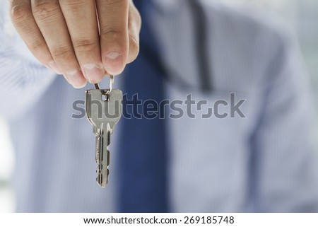Serious man offering key to Your dream - stock photo