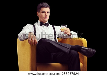 Serious man sitting in an armchair and drinking whiskey on black background