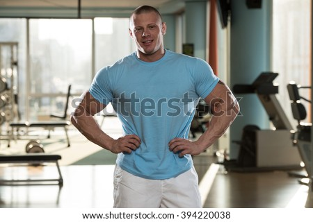 Serious Man Standing In The Gym And Flexing Muscles In T-Shirt - stock photo