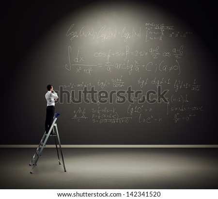 serious man standing on the stepladder and pondering over formulas - stock photo