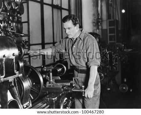 Serious man using large machine - stock photo