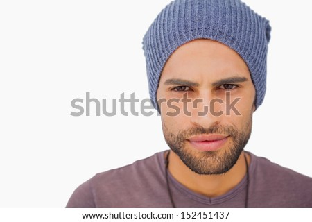 Serious man wearing beanie hat on white background