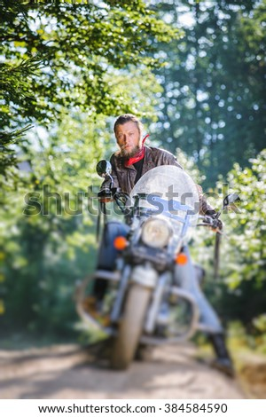 Serious man with beard driving his cruiser motorcycle in the forest. Man is wearing leather jacket and blue jeans. Tilt shift lens blur effect - stock photo