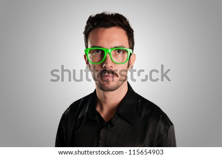 serious man with green eyeglasses on gray background