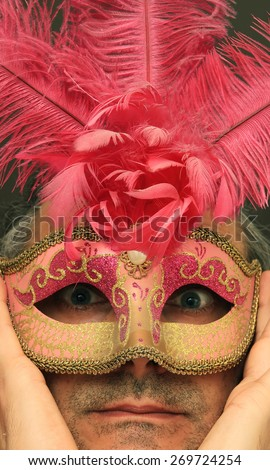 serious man with pink feathers mask  - stock photo