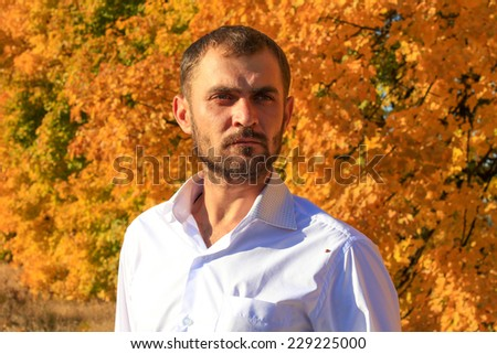 Serious man with the colourful autumn trees at the background - stock photo