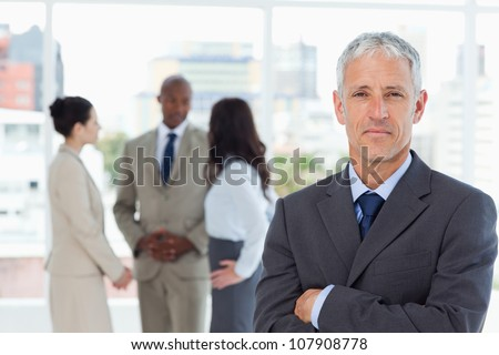 Serious manager crossing his arms while his business team is in the background - stock photo