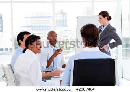 Serious manager giving presentation to her team in the office - stock photo