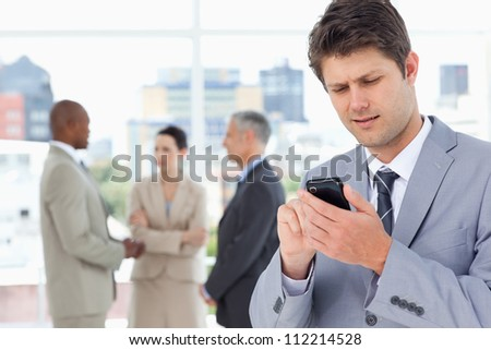 Serious manager sending a text with his mobile phone - stock photo