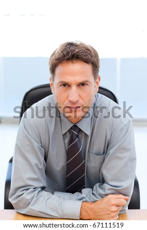 Serious manager sitting at a table in an office - stock photo