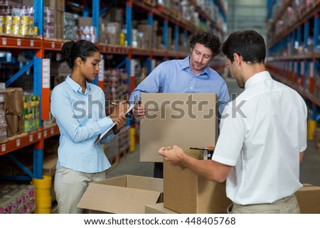 Serious managers are checking some cardboard boxes in a warehouse