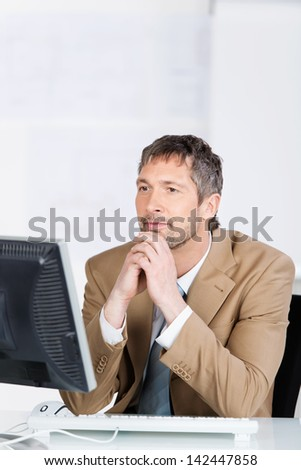 Serious mature businessman looking at computer screen in office - stock photo
