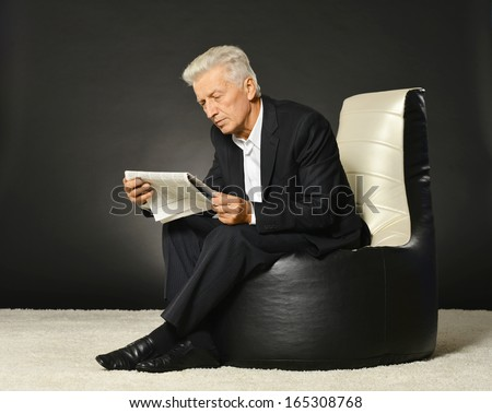 Serious mature businessman portrait sitting on armchair and reading newspaper