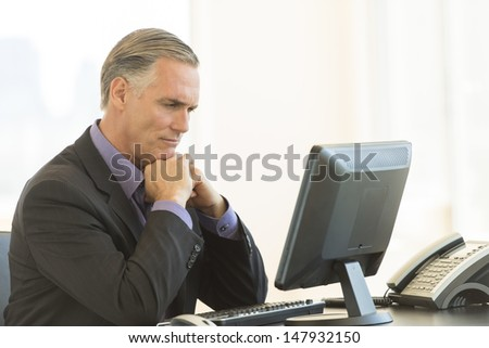 Serious mature businessman with hand on chin looking at desktop PC in office - stock photo