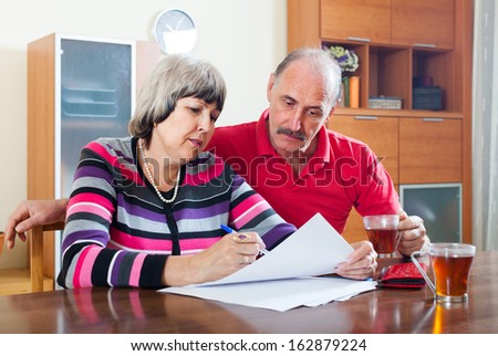 serious mature couple fills in questionnaire together at home interior - stock photo