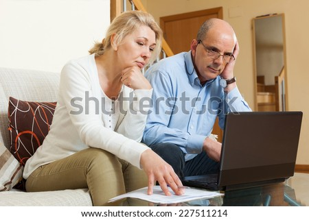 Serious mature couple  with laptop  at table in home - stock photo