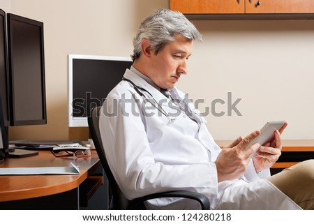 Serious mature male doctor looking at digital tablet while sitting by desk - stock photo