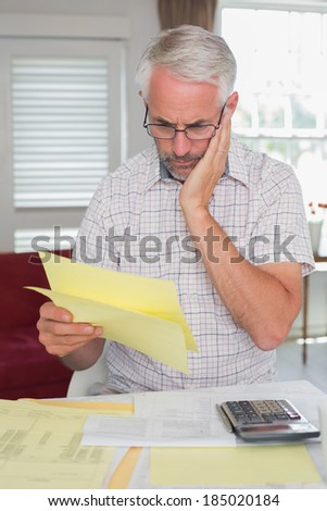 Serious mature man sitting with home bills and calculator at table