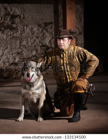 Serious mature medieval mercenary kneeling next to dog - stock photo