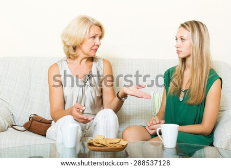 Serious mature mother and daughter talking in home - stock photo