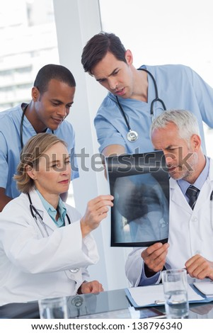 Serious medical team examining radiography in office - stock photo