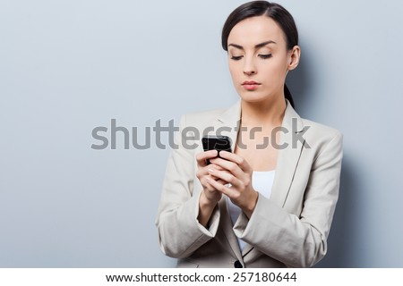 Serious message conversation. Beautiful young businesswoman holding mobile phone and looking at it while standing against grey background - stock photo
