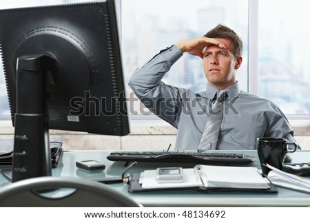 Serious mid-adult businessman reading report on computer screen looking worried and occupied with hand raised to forehead.