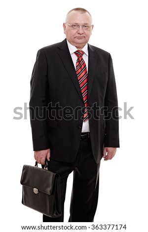 Serious middle aged businessman wearing glasses, red and black striped tie, white shirt and black suit standing with briefcase in his hand isolated on white background - human resources concept - stock photo