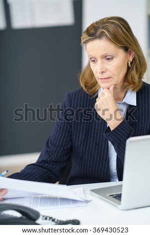 Serious middle-aged businesswoman reading a document as she sits at her desk in the office with a thoughtful expression