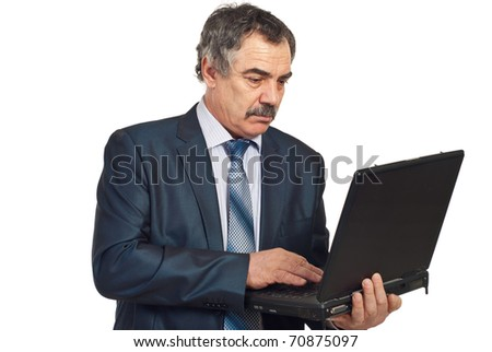 Serious middle aged executive man working on laptop isolated on white background