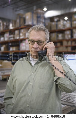 Serious middle aged man using telephone in distribution warehouse - stock photo