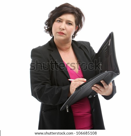 Serious middle-aged secretary listening attentively as she takes minutes at a meeting - stock photo