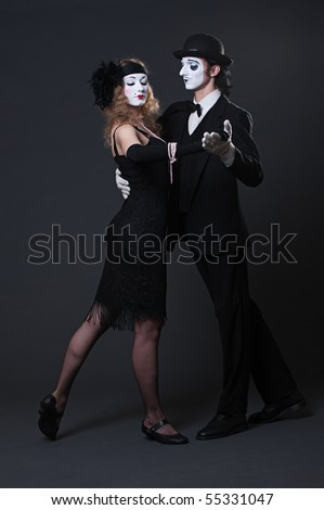 serious mimes dancing over dark background. retro style - stock photo