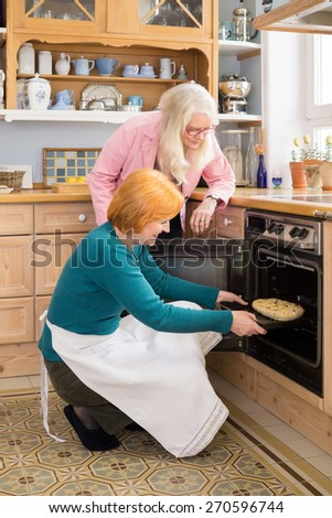 Serious Mom Watching her Happy Active Friend Putting a Cake for their Snacks in an Oven at the Kitchen. - stock photo